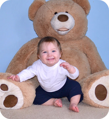 A little boy with a big dimpled grin sitting with a giant teddy bear.