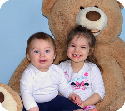 A 3 year old girl and a 11 month old little boy sitting with a giant teddy bear.