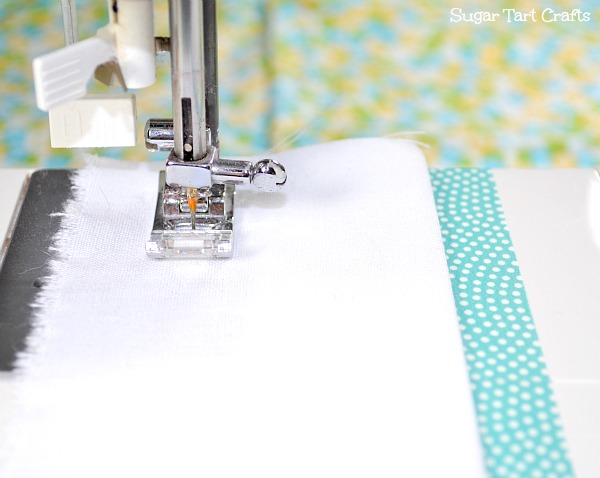 A masking tape line on a sewing machine to help guide the fabric in a straight line