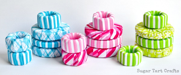 Piles of pattern weights made from washers and nuts wrapped with ribbon.