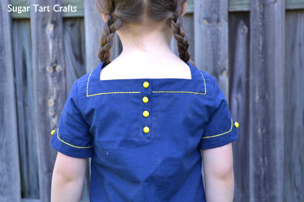 Square neckline with button placket and embroidery.