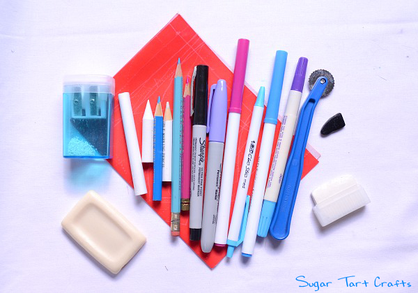 An assortment of pens, pencils, and chalks used on fabric when cutting out patterns.