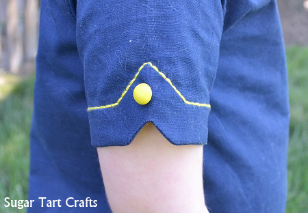 Notched sleeve detail with button and running stitch embroidery.