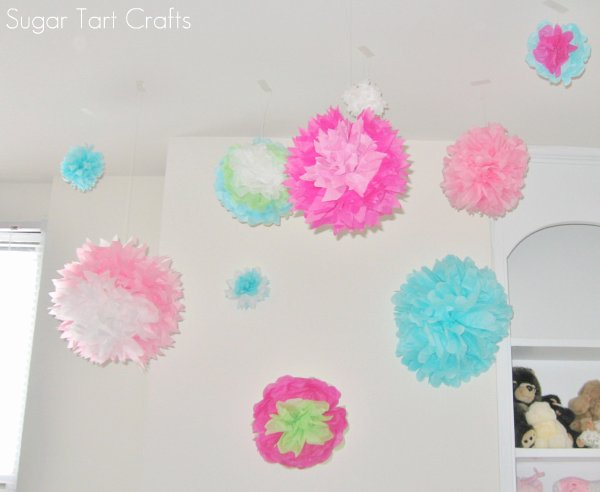 Tissue paper pom poms hanging from the ceiling