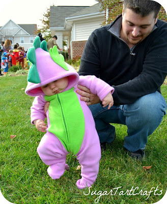 Baby in Spike the dragon costume pretending to stomp