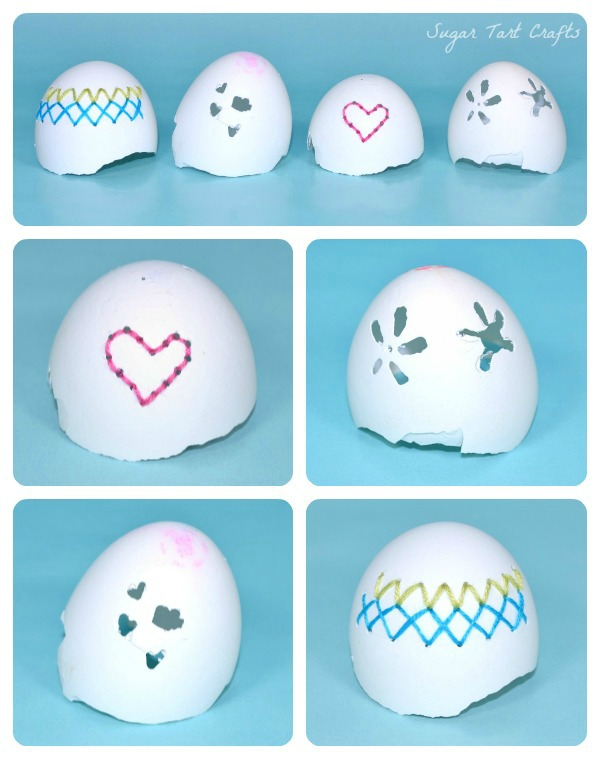 Four eggshells used for dremel practice with holes shaped like hearts, flowers, and embroidery.