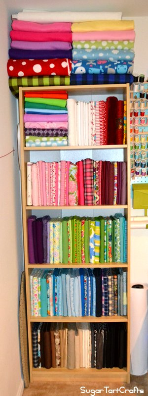 Bookcase full of fabric folded on comic book boards