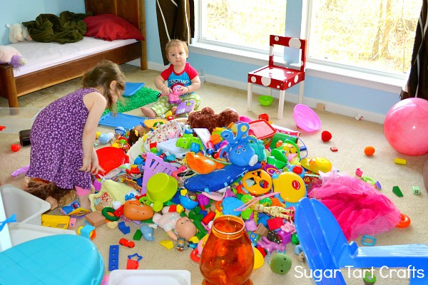 two kids playing with a giant pile of toys